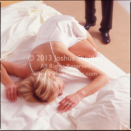 Woman in bed with man's legs in background