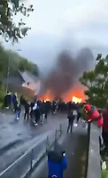 """Pictured: A crown of people some of whom set fire to cars in Waun-Wen Road in the Mayhill area of Swansea, Wales, UK. Thursday 20 May 2021<br /> Re: Gangs of """"yobs"""" have been setting fire to cars and rolling them down a hill in Swansea, Wales, UK.<br /> South Wales Police said they attended """"large scale disorder"""" in the Mayhill area of the city on Thursday evening."""