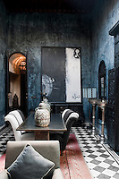 The living/dining area of The Blue Apartment has a black and white tiled floor and bluey/black rag rolled walls which create a dramatic look