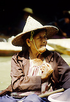 An old woman selling produce on the floating market outside of Bangkok, Thailand