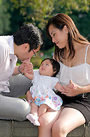 A loving mom and dad with baby in Central Park