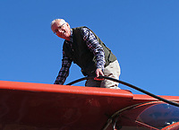 Seaplane pilot Paul Thomas fuels his Helio Courier on floats in Vareness, Quebec