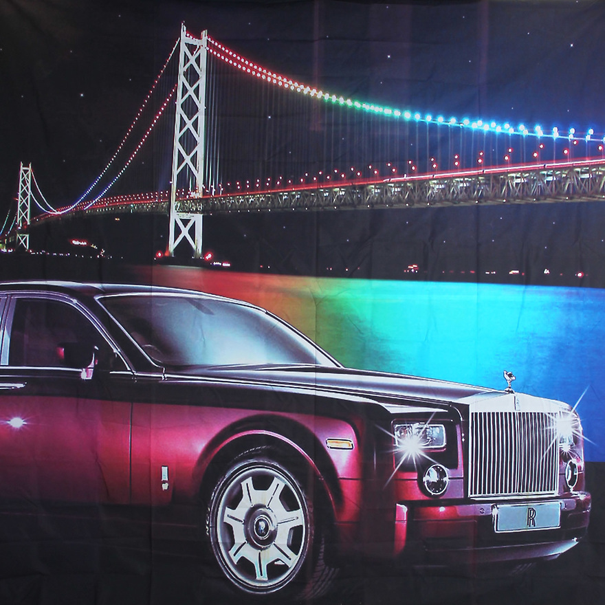Backdrop featuring Rolls Royce luxury automobile car with a bridge in the background and city skyline and skyscraper lights at night