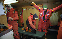 """Crewmen on board the fishing vessel Kiska Sea get ready to go out on deck during the opilio crab season in the Bering Sea.  In this photo they wear a combination of Mustang suits, waterproof gear,  and sweat shirts and pants.  The Bering Sea is known for having the worst storms in the world.  Crab fishing in the Bering Sea is considered to be one of the most dangerous jobs in the world.  This fishery is managed by the Alaska Department of Fish and Game and is a sustainable fishery.  The Discovery Channel produced a TV series called """"The Deadliest Catch"""" which popularized this fishery."""