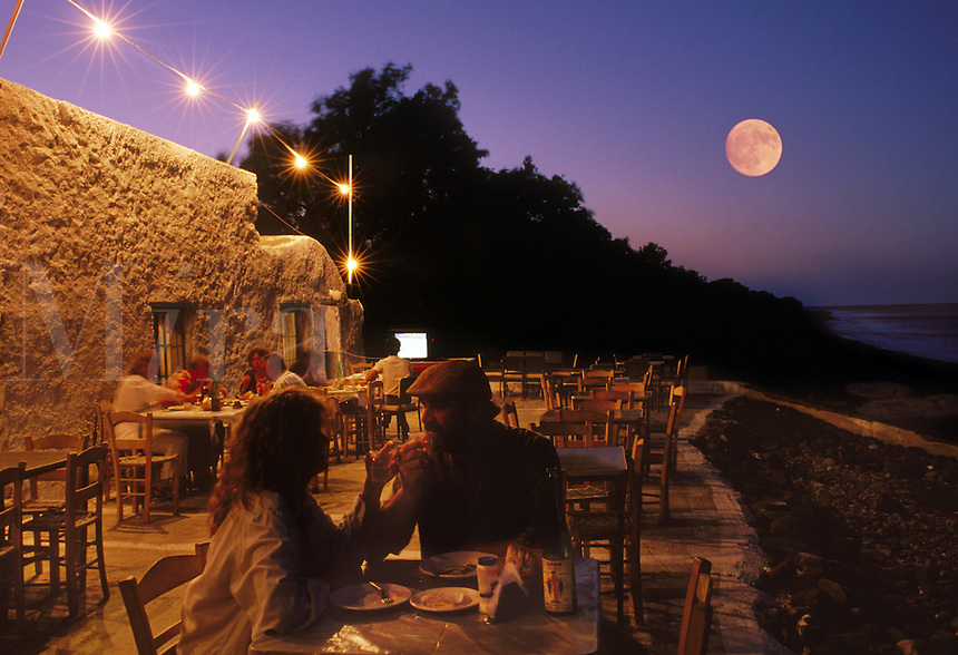 American and European tourists enjoy a drink and fresh fish at an outdoor cafe; town of Monolithos; Island of Santorini; Greece