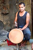 Fes, Morocco.  Metalworker Hammering a Copper Pot in the Seffarine Square (Place Seffarine).