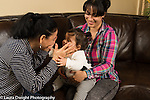 12 month old baby girl held by mother as grandmother plays peek-a-boo game with hands