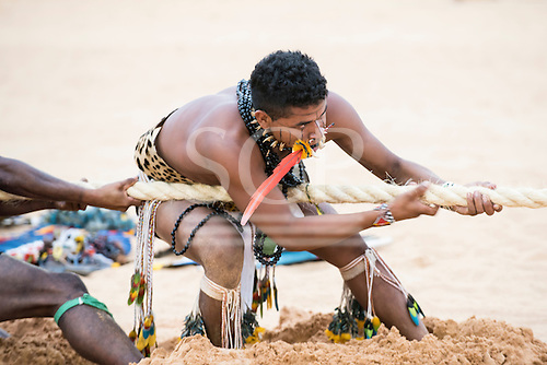 A Brazilian indigenous contestant strains on the rope during the tug of war contest at the International Indigenous Games, in the city of Palmas, Tocantins State, Brazil. Photo © Sue Cunningham, pictures@scphotographic.com 25th October 2015