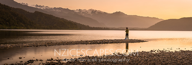 Fishing on pristine Lake Mapourika under Southern Alps at sunset, Westland Tai Poutini National Park, West Coast, UNESCO World Heritage, South Island, New Zealand, NZ