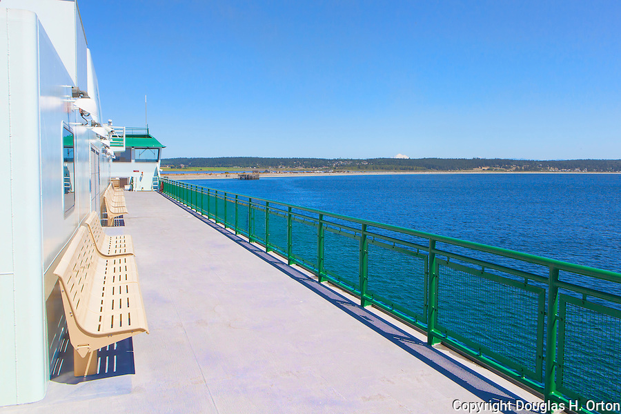 Deck of Washington Stae Ferry, no people, open deck, benches, rail, stunning water view of Whidbey Island.