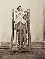 BNPS.co.uk (01202 558833)<br /> Pic: ForumAuctions/BNPS<br /> <br /> Pictured: A striking image shows a prisoner in chains with a head poking through a board covered in Chinese symbols, perhaps listing his misdemeanours.<br /> <br /> Rarely seen 150 year old photos taken by one of the first British photographers to explore China have emerged for sale for £20,000.<br /> <br /> Scotsman John Thomson (1837-1921) travelled to the Far East in 1868 and established a studio in Hong Kong, using it as a base to explore remote parts of the vast country for the next four years, photographing landmarks, scenery and the native population.<br /> <br /> In many cases, he was the first Westerner the people he photographed had encountered.<br /> <br /> One striking image shows a prisoner in chains with a head poking through a board covered in Chinese symbols, perhaps listing his misdemeanours. In another, a man poses next to a giant camel statue in the grounds around the Ming tombs of the Forbidden City.<br /> <br /> Almost 100 of his photos feature in a rare first edition of 'Thomson Illustrations of China and Its People' (1873), which is going under the hammer with London-based Forum Auctions.