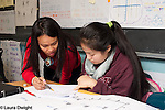 Education High School STEM class female teacher working with female student on project