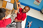 Education preschool first days of school 3-4 year olds two boys playing together with toy plastic dinosaurs