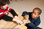 Education preschool 3-4 year olds block area two boys playing together with toy police car and human figure pretend play talking horizontal