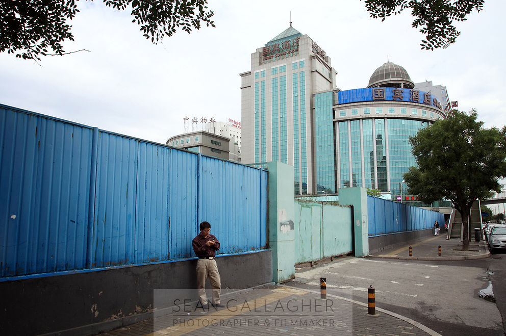 CHINA. Beijing. A man using his cellphone in central Fuchengmen district. 2009