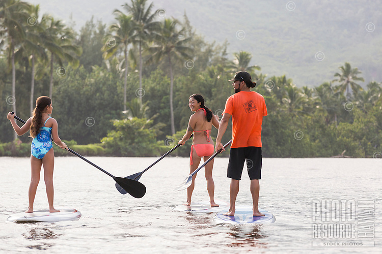 A mother looks back with a smile during a family standup paddling lesson on the Wailua River, Kaua'i.