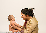 Infant boy age 6 months with mother interaction listening to her talk