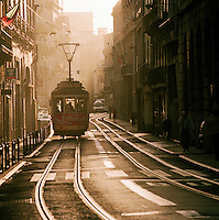 A tram heads down a central street in downtown Lisbon, early in the morning. Lisbon, Portugal