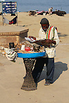 A mobile snack vendor on the banks of the Ganges River catches up on the news while waiting for customers.