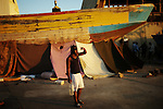 ZANZUR, Libya 9th September 2011:..Man pauses in front of typical Zanzur home a dry-docked boat with tarp stretched down providing protection form the sun, but little else.  ...Ayman Oghanna