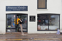 Pictured: A young man empties a bucket of water from a hairdresser's in New Road.<br /> Re: Cleanup after storm Dennis in Crickhowell, Wales, UK.