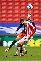 20th February 2021; Bet365 Stadium, Stoke, Staffordshire, England; English Football League Championship Football, Stoke City versus Luton Town; James Bree of Luton Town clears the ball over Nick Powell of Stoke City
