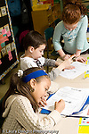Education Elementary school Grade 2 children in class working on English language arts worksheets vertical