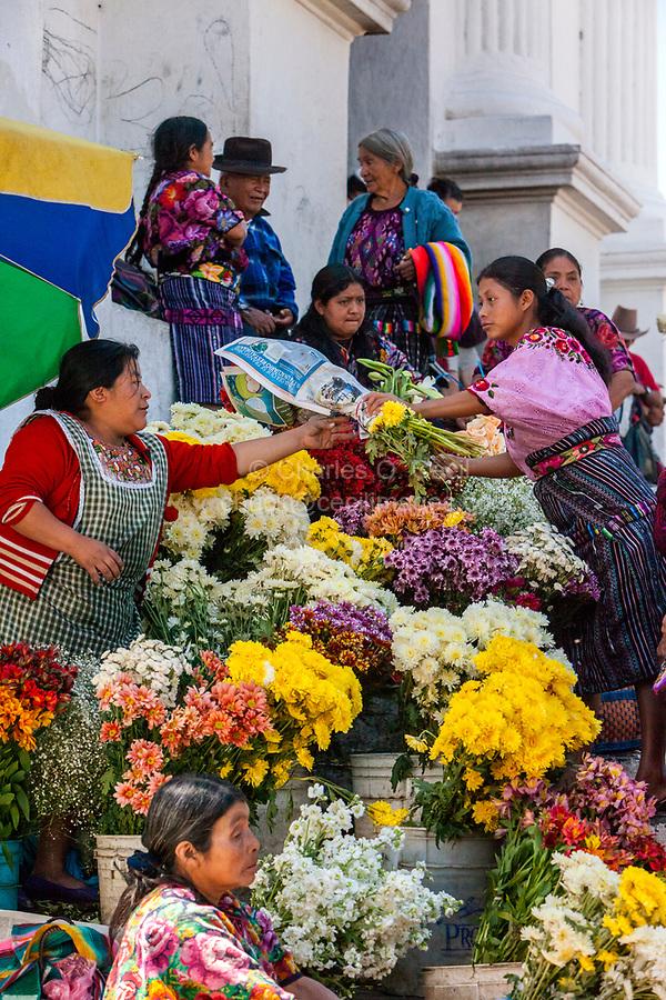 Chichicastenango, Guatemala.  Quiche (Kiche, K'iche') Women Buying and Selling Flowers outside the Church of Santo Thomas, Sunday Morning.