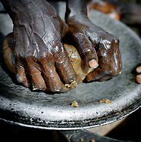 A woman kneads ground peanuts. The oily paste is left to dry in the midday sun and used as a flavouring for bland food. Women grind and mix the peanuts with their bare hands often making enough to last them a whole year. A small bag of peanuts costs 25 CFA (GBP 0.03p) from Meme market.<br /> The extreme north of Cameroon is suffering a food shortage exacerbated by climate change and conflict with Boko Haram. Fighting has spread across the borders from Nigeria into the countries of the Lake Chad region creating a refugee and famine crisis. Once an intrepid tourist destination boasting Waza national park, the extreme north of Cameroon now hosts people fleeing violence housed in unnamed refugee camps where they are lucky if they manage to get a single meal each day.