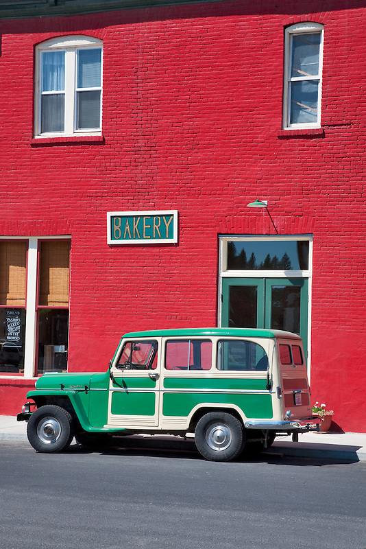 Antique Willy's parked in front of red buiding. Palouse, Washington.
