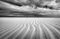 Ripples in the sand created by a strong wind as a storm approaches.