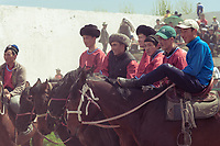 Kok Boru players watching the horse races before their game is due to start. Kok-boru is a popular horse game in Kyrgyzstan in which two teams of riders try to carry a goat or calf carcass into the opposing teams endzone.