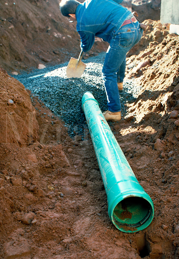 Drinage pipe in hole, with worker and gravel, vert. Hartford CT USA.