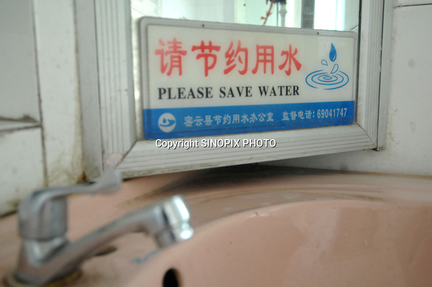 """A sign """"Please save water in a toilet.  The ten-year drought in northern China has meant that the reservoir is at just 25% of capacity. Beijing is pumping in water from southeren areas for the Olympics"""