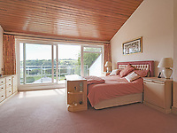 BNPS.co.uk (01202) 558833. <br /> Pic: LillicrapChilcott/BNPS<br /> <br /> Pictured: Bedroom. <br /> <br /> This impressive waterfront home with breath-taking views is the perfect property for a wannabe sailor - on the market for £2.5m.<br /> <br /> Huefield sits in an elevated position looking over the rooftops of neighbouring properties onto the beautiful Helford River in Cornwall - ideal for watching boats coming and going.<br /> <br /> The Helford Passage area is so sought after houses rarely come up for sale and this one, on the market with Lillicrap Chilcott, is the only property available there at the moment.<br /> <br /> The five-bedroom home is south facing and has a swimming pool and beautiful gardens for enjoying the view, as well as access to a gate with a right of way down to the water.