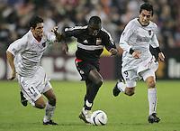 30 October,  2004.   DC United's Freddy Adu (9) splits the defense of the MetroStars' Pablo Brenes (11) and Sergio Galvan Rey (9) during the 2004 MLS playoffs at RFK Stadium in Washington, DC.