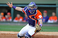 Freshman catcher Chris Okey (25) of the Clemson Tigers reaches for a wide throw in the Reedy River Rivalry game against the South Carolina Gamecocks on March 1, 2014, at Fluor Field at the West End in Greenville, South Carolina. South Carolina won, 10-2.  (Tom Priddy/Four Seam Images)