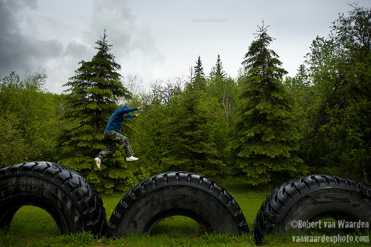 """Simon Reece from Anzac, Alberta, jumps from giant tire to giant tire, a signal of the industrial development in the region. """"We are the land, and the land is us and all of our teachings and values stem from that one."""""""