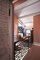 An ironwork balustrade by Jean Bernard encloses a central spiral staircase on the upstairs landing of the property