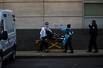 Medical workers wheel a patient arriving by ambulance to the emergency room at Maimonides Medical Center on March 28, 2020 in Brooklyn, NY.  NYC's daily death toll from the coronavirus nearly tripled from the previous 24-hour period from 85 on Friday to 222 on Saturday.  Photograph by Michael Nagle/Redux