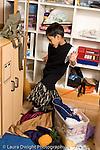 Education preschoool children ages 3-5 pretend play boy in family area looking at himself in mirror wearing dressup dress vertical