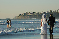"""James McNamara of St Louis and his wife Jessie (nee Donahoe) from San Diego walk along the shore in Pacific Beach, Wednesday February 27 2008.  The couple married on Crystal Pier last Saturday and were on the beach to """"Trash the Dress"""" with their wedding photographer taking some shots for the website of that name (www.trashthedress.com)."""