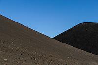 A woman hikes up a trail on Mauna Kea, Big Island of Hawai'i.