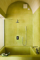 A contemporary bathroom with a sunken bath with walls decorated in 'cocciopesto', an Italian lime mortar that contains fragments of pottery