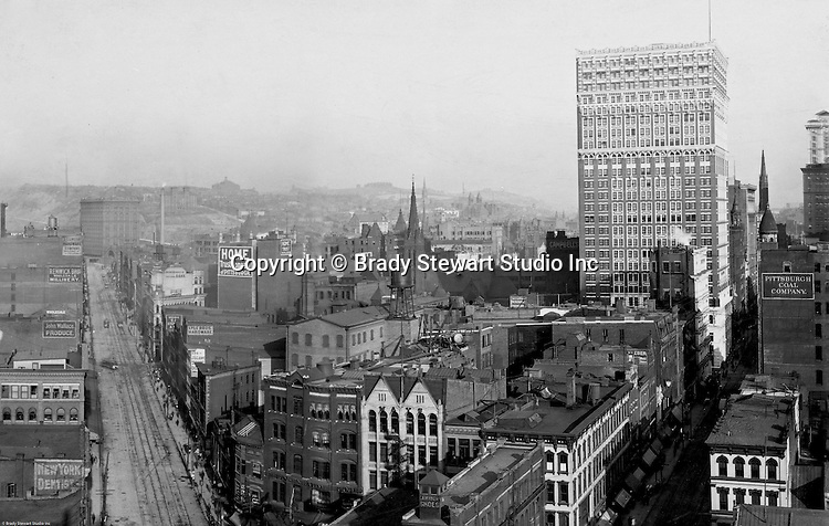 Pittsburgh PA: View of City from the top of the Empire Building. View of the city looking up Liberty Avenue towards the Pennsylvania Railroad Station. The Farmers Bank Building is on the right. View of three sets of trolley tracks on Liberty Avenue. Company signs on city buildings included: C.A. Verner Shoes, CA Verner Shoes, Home Trust Company of Pittsburgh, JC Lindsay Hardware Company, John Wallace Produce, JR Weldin & Company Stationery, Lyle Bros Hardware, Monongahela National Bank, Pittsburgh Coal company sign, Renwick Bros Wholesale Millinery, Rosenbaum Company