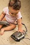 Infant development 9 month old baby girl playing with telephone
