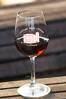 Glass of red wine embossed with Chateau Mire l'Etang La Clape. Chateau Mire l'Etang. La Clape. Languedoc. France. Europe.