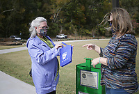 """Karen Wagaman, vice president of downtown development for the Rogers-Lowell Area Chamber of Commerce, (from left) and Trish Ouei, urban stormwater educator, look through a trash-pickup supply bag, Thursday, October 15, 2020 at Lake Atalanta in Rogers. The third annual Great Arkansas Cleanup has kicked off as a no-contact cleanup where community volunteers are invited to pick up trash around the paved and soft trails, along the creek - both upstream and downstream of Lake Atalanta in Rogers - and other areas. <br /> <br /> For the past two years, Lake Atalanta Appreciation Day has been held in conjunction with Earth Day but was postponed due to covid-19. Because of the coronavirus pandemic, NWA parks and trails are seeing an increase in the number of people using the parks as people move outdoors for entertainment and exercise. <br /> <br /> Organizers selected the last two weeks of October to encourage the community to """"pick up where you play"""" while enjoying the park. <br />  <br /> Participants can pick up trash bags and gloves at one of seven green supply bins located in various areas of Rogers including Clark Pavilion at Lake Atalanta Park.<br /> <br /> Check out nwaonline.com/2010013Daily/ for today's photo gallery. <br /> (NWA Democrat-Gazette/Charlie Kaijo)"""