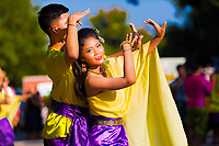Thai dance couple in beautiful, traditional, yellow and purple dresses during Loy Krathong festival celebrations in Sukhothai Historical Park, Thailand