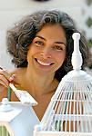 Mature woman painting bird cage